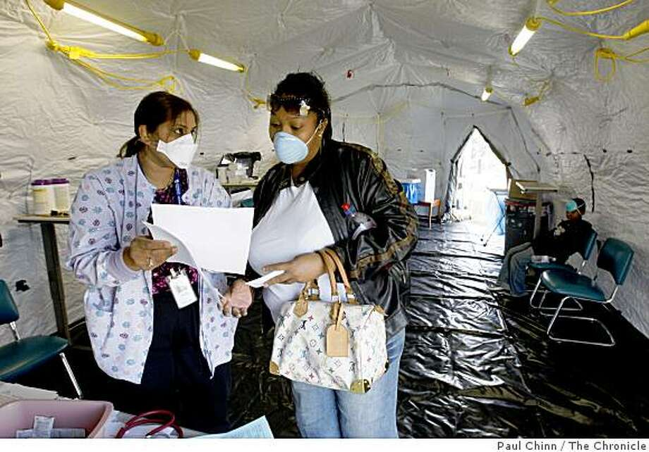 Registered nurse Sujeeta Sukhu (left) describes swine flu symptoms to Courtney Moore who brought her son Daniel Johnson (far right) to the hospital with a sore throat at Sutter Delta Medical Center in Antioch, Calif., on Thursday, April 30, 2009. Photo: Paul Chinn, The Chronicle