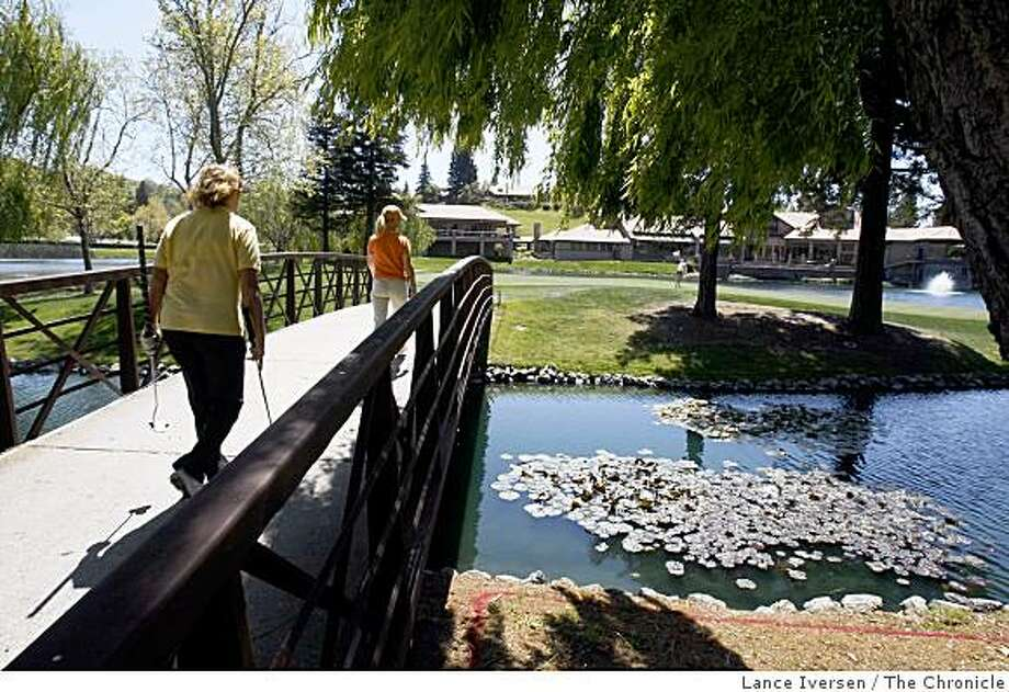 Member of Blackhawk Country Club cross a bridge to reach the 18th green. Country club's throughout California including Blackhawk in Danville are for the first time seeing a slowdown in membership do to the troubled economic times. Thursday April 16, 2009. Photo: Lance Iversen, The Chronicle