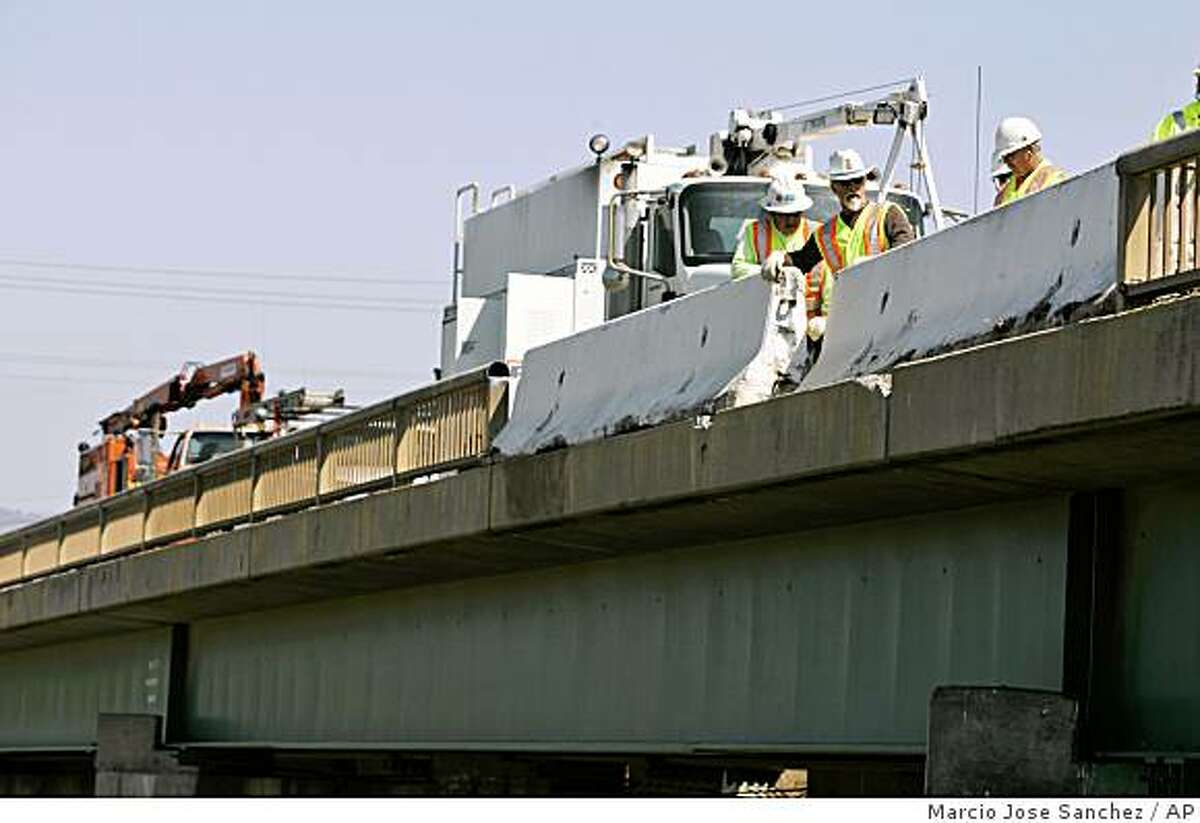 CalTrans workers repair a bridge railing that was damaged during a tour bus accident in Soledad, Calif., Wednesday, April 29, 2009. A bus carrying French tourists through California overturned on a highway overpass in a horrific crash that killed at least five people and left dozens injured. Investigators are still trying to determine the cause of Tuesday's crash, which shut down the Central California highway for hours. (AP Photo/Marcio Jose Sanchez)