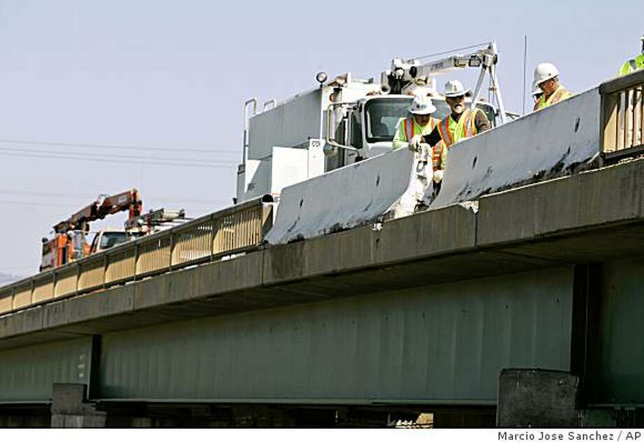 CalTrans workers repair a bridge railing that was damaged during a tour bus accident in Soledad, Calif., Wednesday, April 29, 2009.  A bus carrying French tourists through California overturned on a highway overpass in a horrific crash that killed at least five people and left dozens injured. Investigators are still trying to determine the cause of Tuesday's crash, which shut down the Central California highway for hours.  (AP Photo/Marcio Jose Sanchez) Photo: Marcio Jose Sanchez, AP