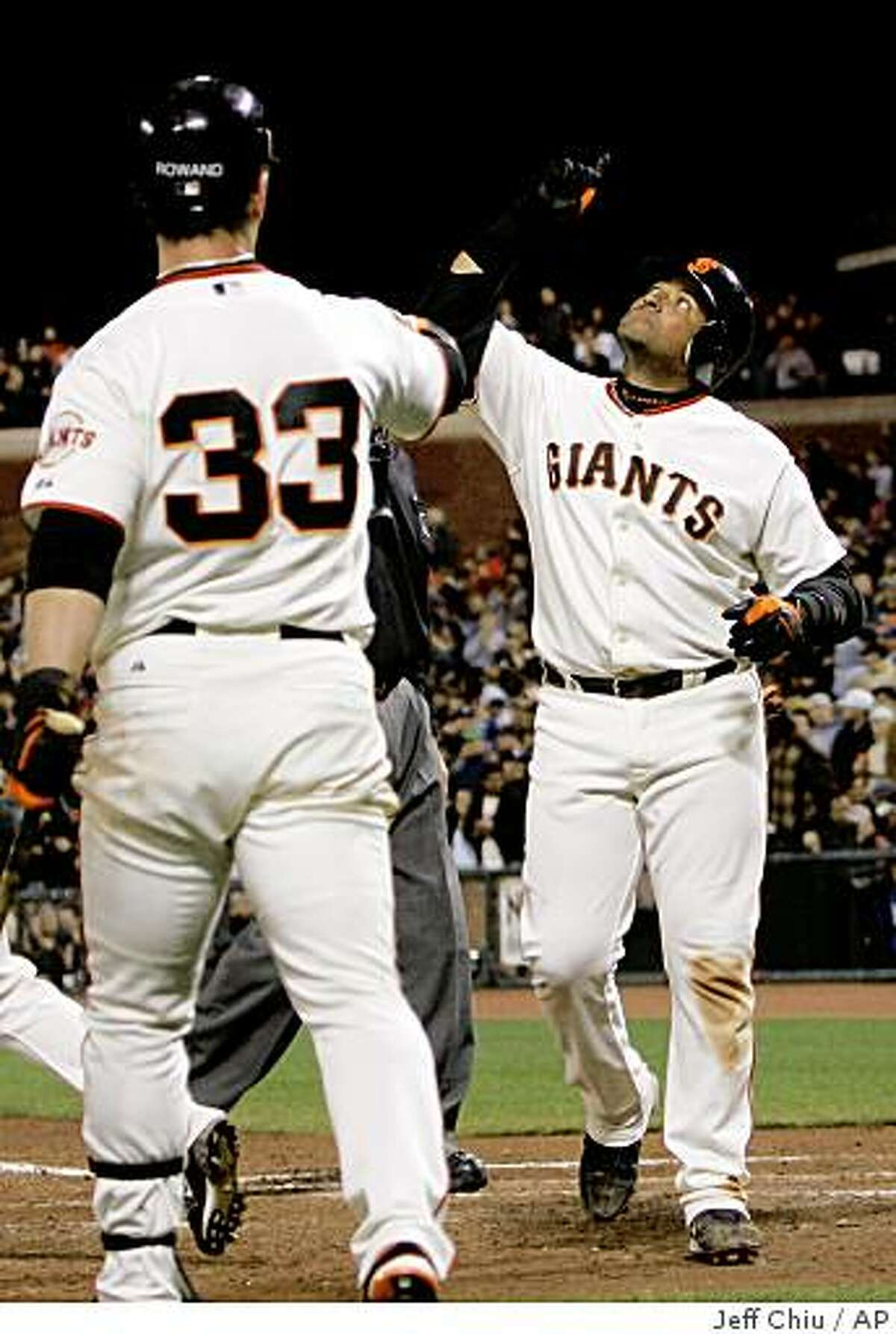 San Francisco Giants' Bengie Molina, right, celebrates after hitting a solo home run off of Los Angeles Dodgers' Scott Elbert in the seventh inning of a baseball game in San Francisco, Wednesday, April 29, 2009. At left is Giants' Aaron Rowand.