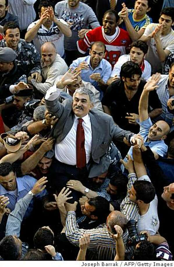 Lebanese men carry on their shoulders former domestic security chief Ali Hajj upon his arrival home from prison in Beirut on April 29, 2009.  Lebanon released four generals who had been held for nearly four years without charge over the assassination of ex-premier Rafiq Hariri following a ruling by a UN-backed court. The four, considered pro-Syrian, were escorted separately out of Roumieh prison on the outskirts of Beirut in a convoy of vehicles after The Hague-based Special Tribunal for Lebanon said there was insufficient evidence to charge them.     TOPSHOTS/AFP PHOTO/JOSEPH BARRAK (Photo credit should read JOSEPH BARRAK/AFP/Getty Images) Photo: Joseph Barrak, AFP/Getty Images
