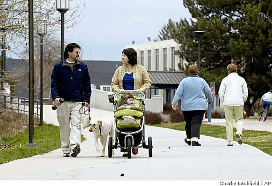 ** ADVANCE FOR SUNDAY, APRIL 26 **In this April 9, 2009 photo, Boise State University professor Michael Humphrey walks with his wife, Marcy, and their 2-year-old daughter, Annelise, and family dog along the west end of the university campus in Boise, Idaho. Humphrey is one of five faculty members at Boise State who live in residence halls to oversee both the personal and academic well being of the students. (AP Photo/Charlie Litchfield) Photo: Charlie Litchfield, AP