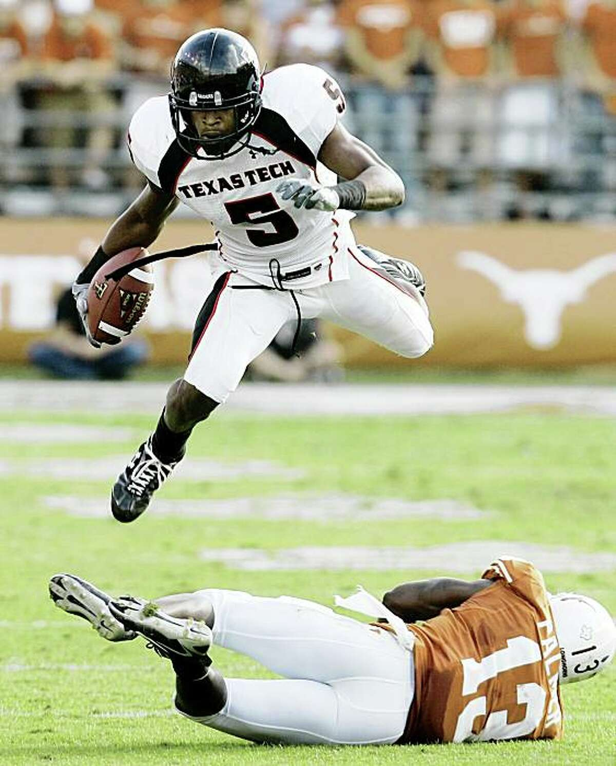 ** FOR USE AS DESIRED WITH NFL DRAFT STORIES ** FILE - In this Nov. 10, 2007 file photo, Texas Tech wide receiver Michael Crabtree (5) leaps over Texas defender Ryan Palmer (13) during the second quarter of an NCAA college football game in Austin, Texas. Crabtree is a top prospect in the 2009 NFL Draft. (AP Photo/Eric Gay, File)
