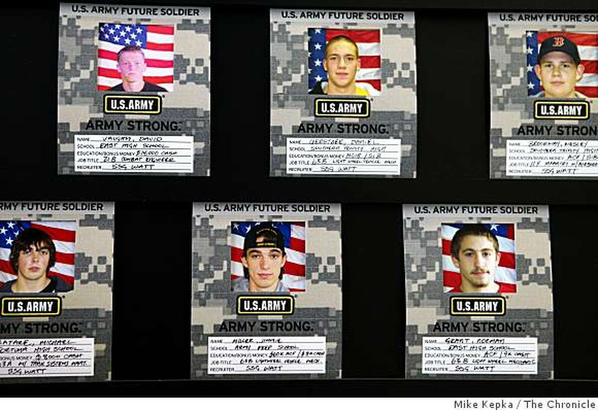 Photographs of new recruits line a well-lit wall at the Army recruiting office in Eureka, Calif.