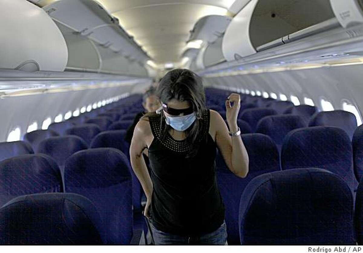 A passenger wearing a protective mask exits a plane upon arrival from San Salvador and Guatemala to Mexico at the Benito Juarez International Airport in Mexico City, Monday, April 27, 2009. A fatal strain of swine flu has been detected in Mexico and believed to have killed 149 people, while the virus has been confirmed or suspected in at least a half-dozen other countries. (AP Photo/Rodrigo Abd)