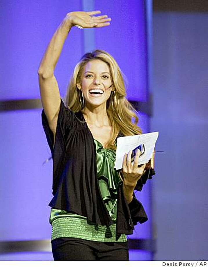 Miss California Carrie Prejean waves as she comes on stage at the Rock Church during services in San Diego Sunday, April, 26, 2009. Prejean has drawn attention for her comments against gay marriage at the Miss USA pageant, where she was first runner-up last weekend. (AP Photo/Denis Poroy) Photo: Denis Poroy, AP