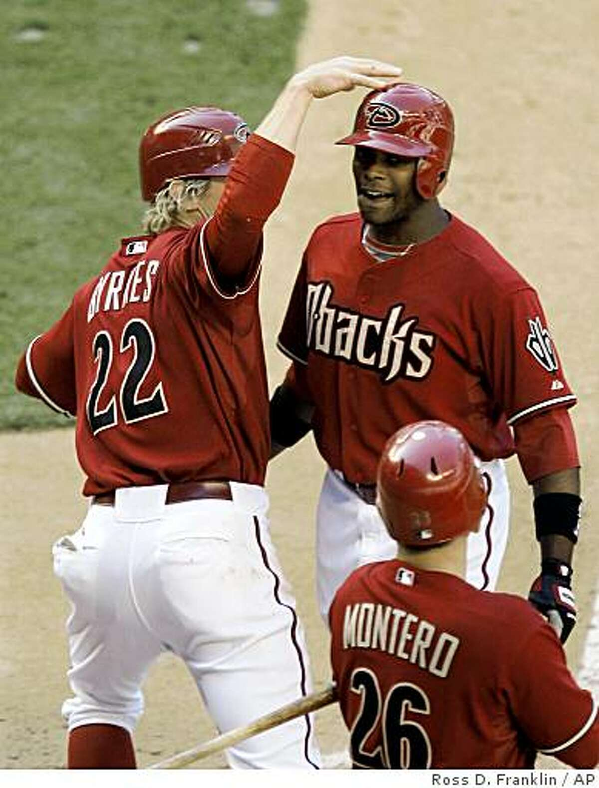 Arizona Diamondbacks' Justin Upton, top right, celebrates his game-tying home run with teammates Eric Byrnes (22) and Miguel Montero (26), of Venezuela, in the ninth inning of a baseball game against the San Francisco Giants Sunday, April 26, 2009, in Phoenix. (AP Photo/Ross D. Franklin)
