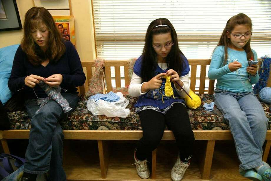 (L-R) Michelle Tartaglio and her daughters Melissa, 10, and Sarah, 7, knit, during a workshop at the Stratford Public Library teaching people how to knit scarves and hats for children's charities, Monday, Nov. 2, 2009. Photo: Phil Noel / Connecticut Post