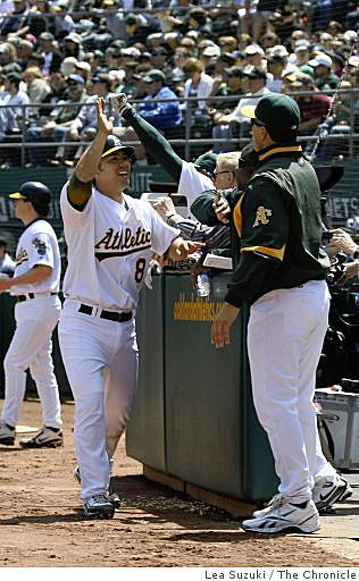 Kurt Suzuki (left) celebrates his run with teammates in the bottom of the second after scoring on Ellis' single to center during the Oakland Athletics vs, Tampa Bay Rays game on Sunday April 26, 2009 in Oakland.