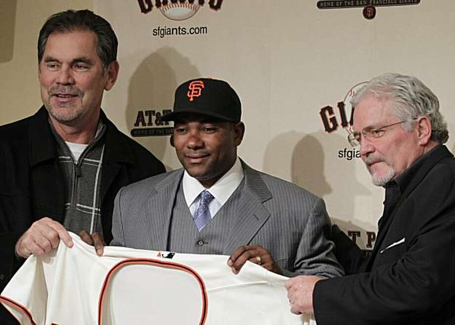 San Francisco Giants new shortstop Miguel Tejada, center, holds up a jersey with manager Bruce Bochy, left, and general manager Brian Sabean, right, after being introduced during a news conference at AT&T Park in San Francisco, Thursday, Dec. 2, 2010. Theformer MVP signed a one-year deal with the baseball team. Photo: Eric Risberg, AP