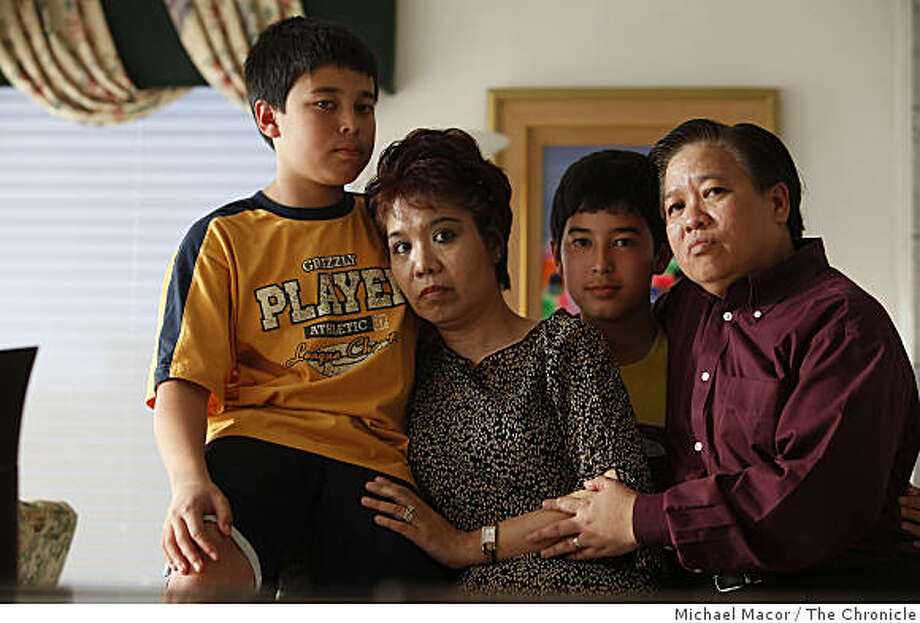 Shirley Tan (second left) poses for a portrait with her 12-year-old twin boys Jashley (left) and Joriene and her partner Jay Mercado in their Pacifica, Calif., home on Wednesday, April 1, 2009. Friday morning Tan will have to surrender herself to U.S.  Immigration for deportation back to the Philippines because she is not a citizen even though her partner of 23 years is a naturalized American citizen. Photo: Michael Macor, The Chronicle