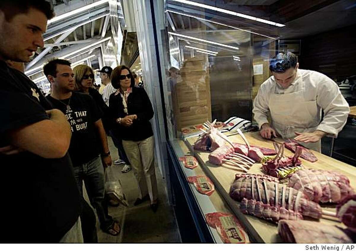 Patrons of the new Yankee Stadium watch butchers preparing meat for one of the premium food stands at the first regular season baseball game at the new Yankee Stadium on Thursday, April 16, 2009, in New York. The Yankees face the Cleveland Indians in their home-opener. The new stadium has a decidedly upstairs-downstairs feel that grates on critics who see it as catering to rich and famous -- but opening day fans may not really care. (AP Photo/Seth Wenig)