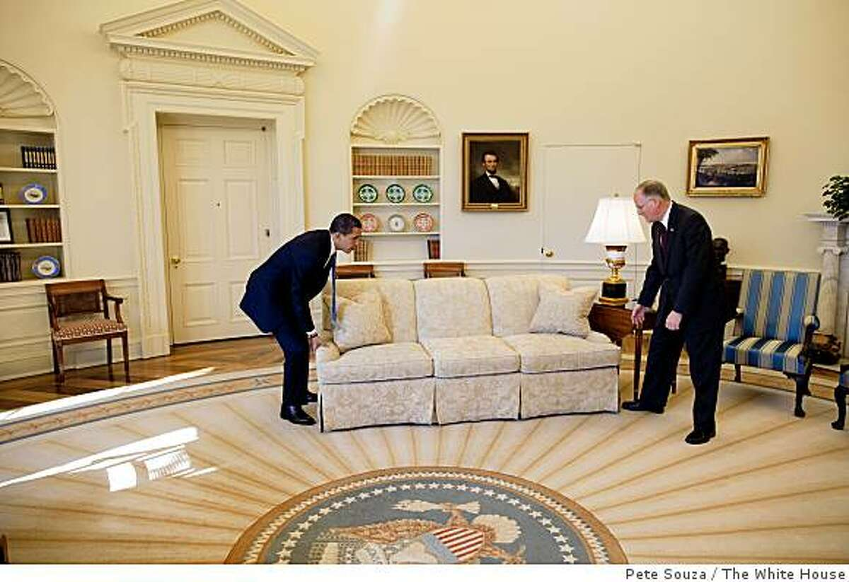 President Barack Obama is helped by Vermont Governor Jim Douglas to move a couch in the Oval Office on February 2, 2009. Governor Douglas met with the President about the economic recovery plan.