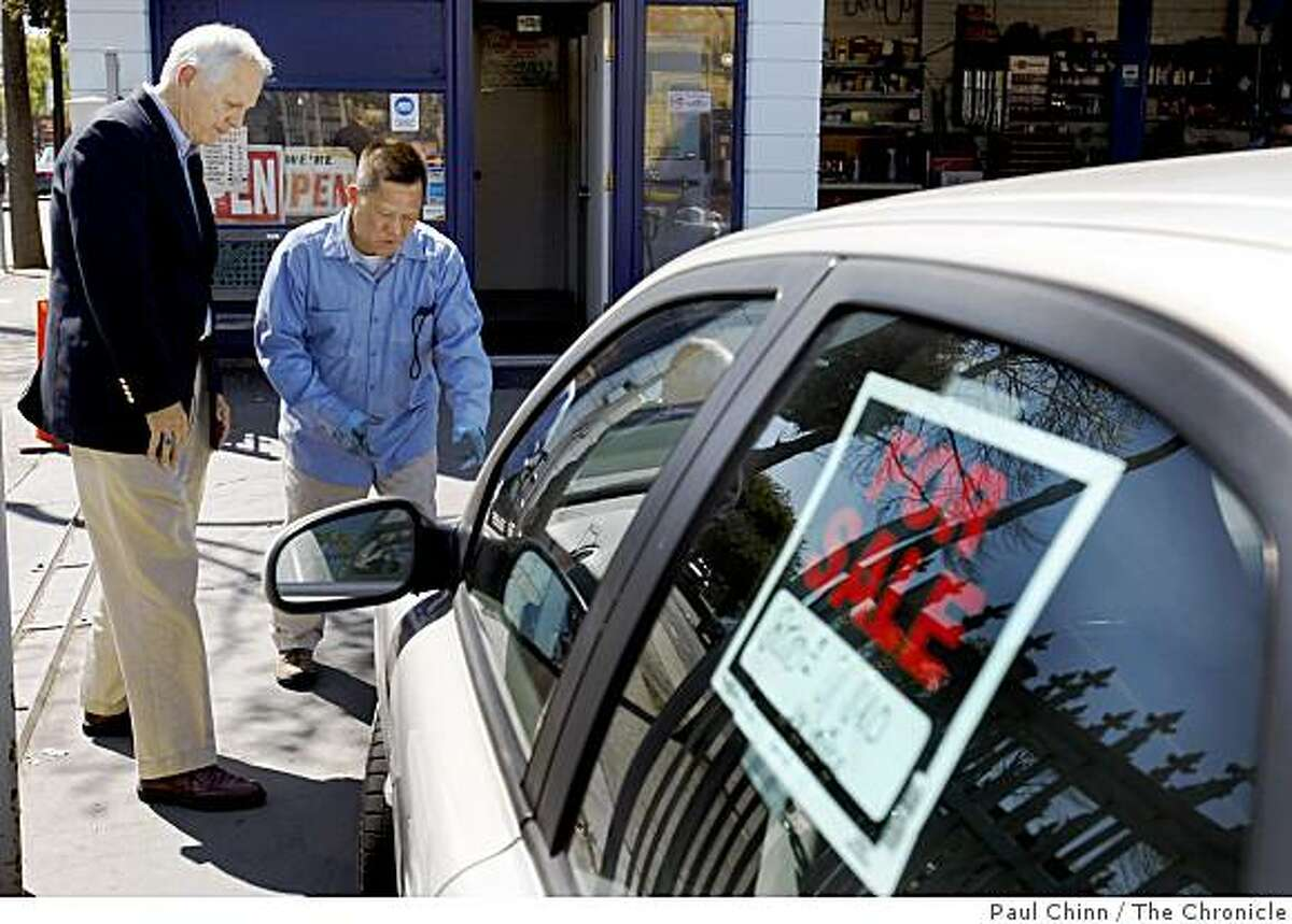 Berkeley Mayor Tom Bates (left) talks about his car with auto mechanic Franklin Young in Berkeley, Calif., on Thursday, April 16, 2009. Young is selling the car for Bates who doesn't need it anymore since he walks and takes public transit everywhere.