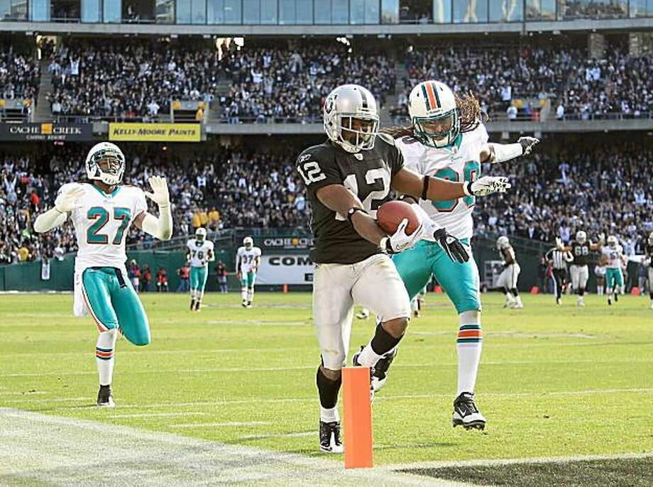 OAKLAND, CA - NOVEMBER 28:  Jacoby Ford #12 of the Oakland Raiders runs past Benny Sapp #27 and Chris Clemons #30 of the Miami Dolphins to score a touchdown at Oakland-Alameda County Coliseum on November 28, 2010 in Oakland, California. Photo: Ezra Shaw, Getty Images