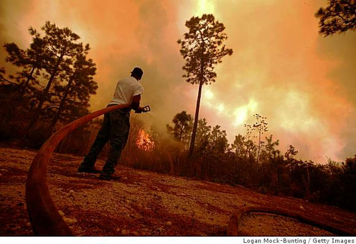 A man sprays water on a raging fire as it threatens nearby homes on April 23, 2009 near Conway, South Carolina. South Carolina Gov. Mark Sanford declared a state of emergency Thursday for a coastal county where a wildfire has consumed thousands of acres and destroyed dozens of homes.