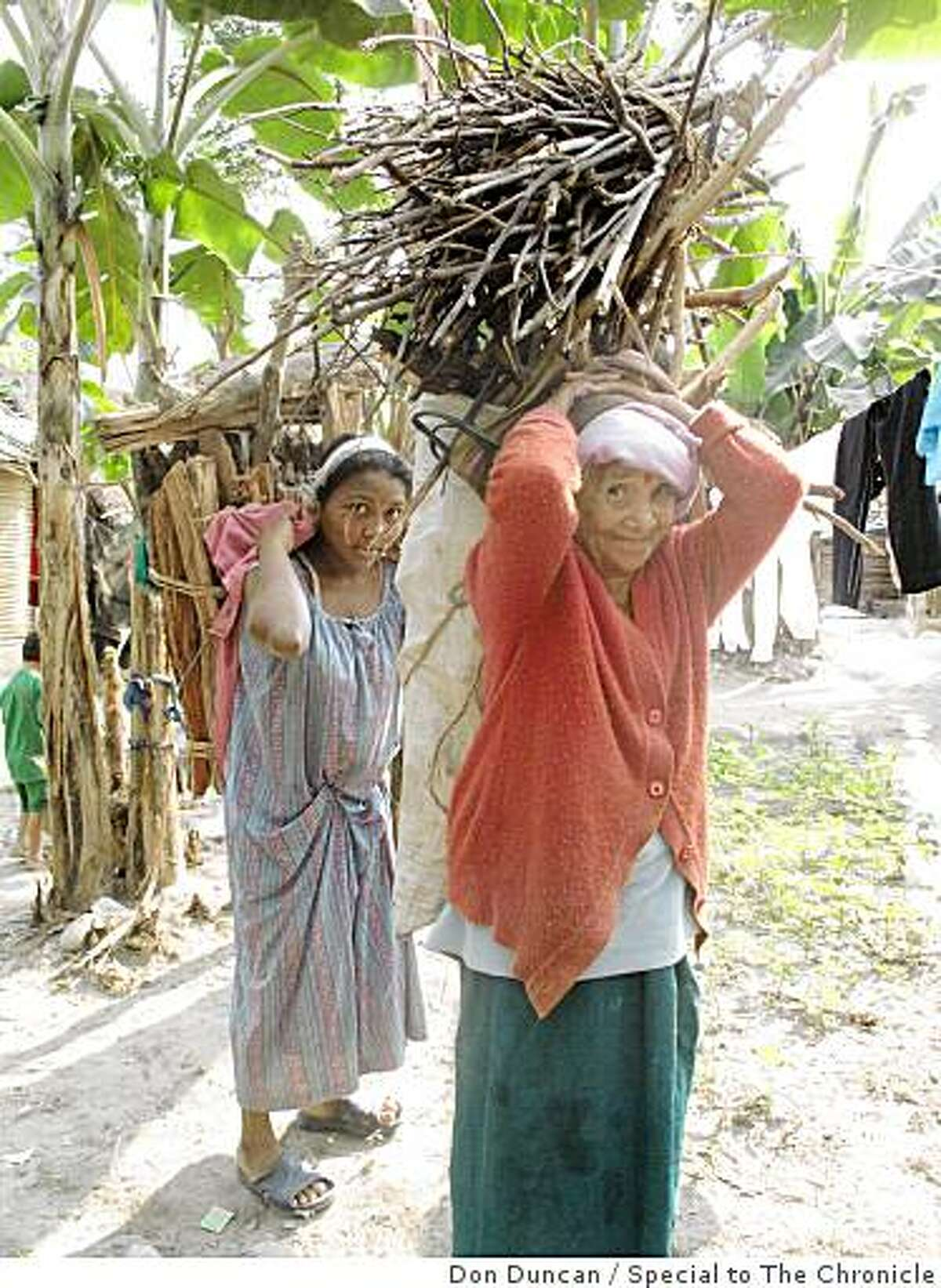 Nepalese refugees from Bhutan carry wood in the Beldangi I refugee camp in eastern Nepal.