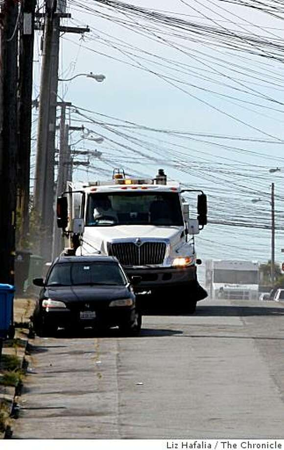 Parking ticket revenue dropped 26 percent last fall when there was a cut in street sweeping last year.  Streetsweeper passes a ticketed vehicle on 35th Ave. near Lincoln Blvd. in San Francisco, Calif., on Tuesday, April 21, 2009. Photo: Liz Hafalia, The Chronicle