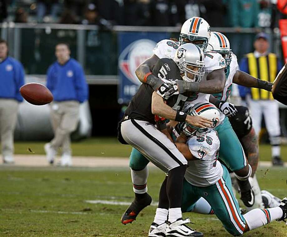 The Raiders' Bruce Gradkowski is sacked and loses the ball in the final minutes of the game against the Miami Dolphins at the Oakland Coliseum on Sunday. Photo: Brant Ward, The Chronicle