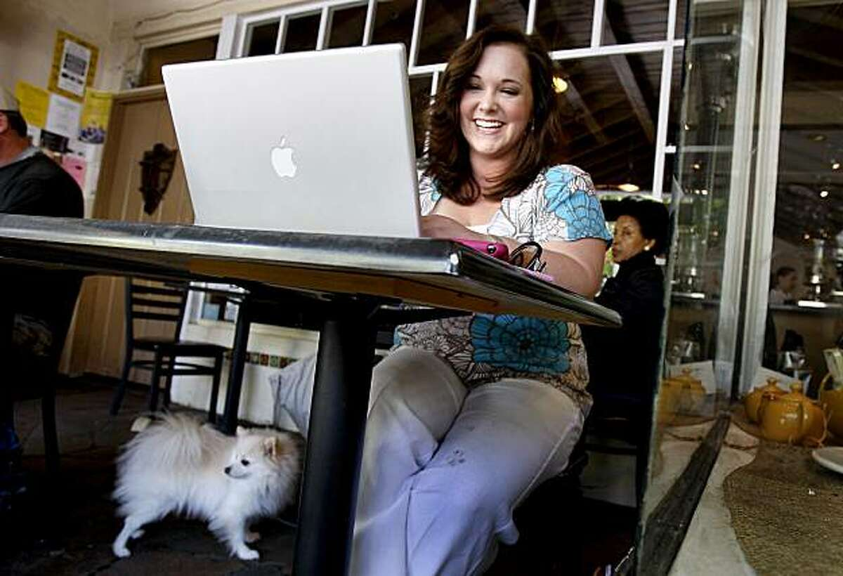 Lauren Bernsen laughs as she reads an email while working on her iPhone application at an outdoor cafe in downtown Palo Alto Thursday April 16, 2009. Her dog, Monte, waits nearby. The iPhone has attracted plenty of developers and programmers, but the alure of the platform even extends to people with no programming background at all.