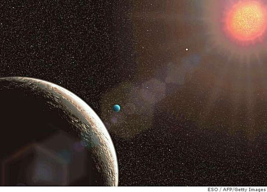 This handout illustration released on April 21, 2009 by the European Southern Observatory (ESO) shows the planet Gliese 581e (blue), the lightest exoplanet discovered so far, as announced by the ESO's La Silla Observatory, north of La Serena, 460 km north of Santiago.  AFP PHOTO/ESO (illustration) (Photo credit should read -/AFP/Getty Images) Photo: ESO, AFP/Getty Images