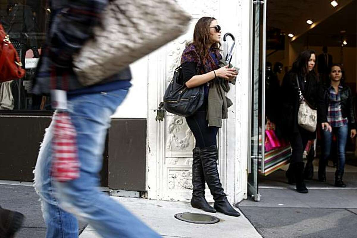 Katie Bradley (center) holds on to her umbrella, like other pedestrians, in case it rains again. Light rain and sun hits San Francisco pedestrians in San Francisco, Calif., on Nov. 27, 2010.