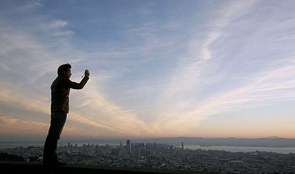 Yoichi Katayama, from Japan and a student at the Haas School of Business at UC Berkeley, takes a picture of the sunrise from Twin Peaks in San Francisco, Friday, Nov. 26, 2010.