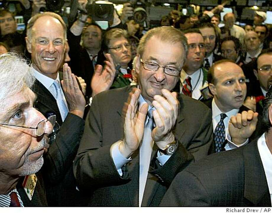 Visa Chairman and CEO Joseph Saunders, center, and company COO John Partridge, upper left, applaud on the floor of the New York Stock Exchange as their company's IPO starts trading, Wednesday, March 19, 2008. Overcoming the jitters that have battered many of the lenders that issue its cards, Visa Inc. sold 406 million shares at $44 apiece late Tuesday to raise nearly $18 billion and complete the most lucrative initial public offering in U.S. history. (AP Photo/Richard Drew) Photo: Richard Drew, AP