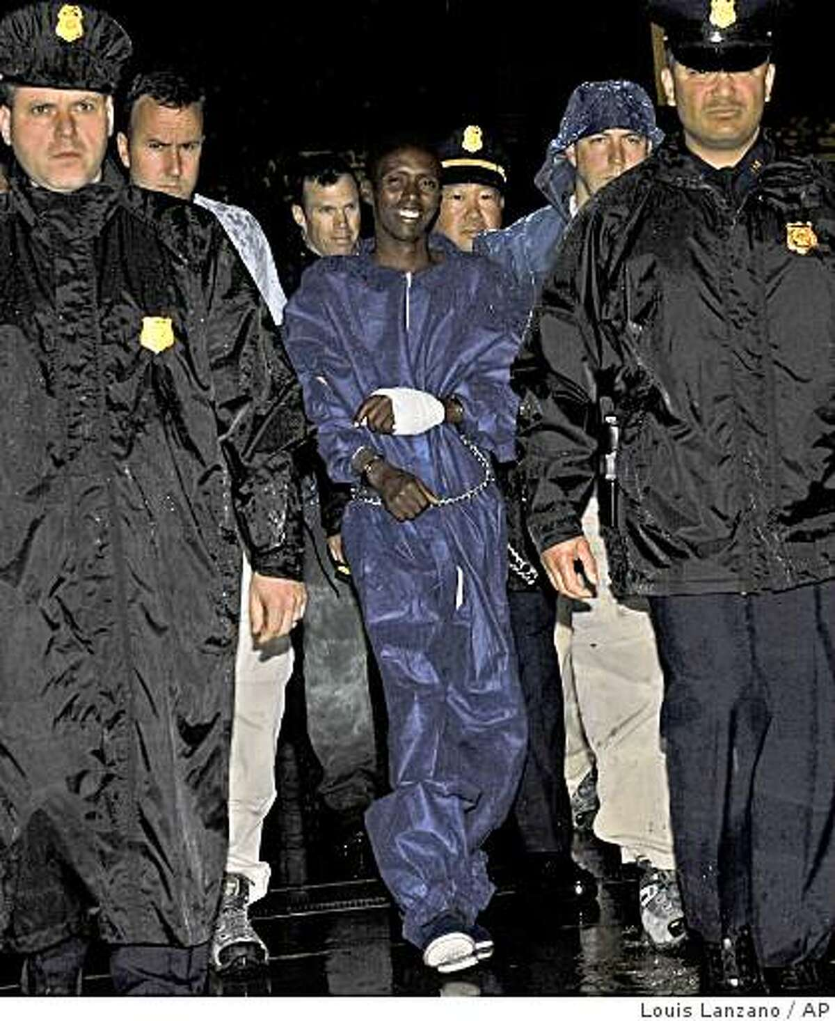 ** CAPTION CORRECTION, CORRECTS SPELLING OF SUSPECT'S NAME TO ABDIWALI ABDIQADIR MUSE, NOT ABDUHL WALI-I-MUSI ** Police and FBI agents escort the Somali pirate suspect U.S. officials identified as Abdiwali Abdiqadir Muse into FBI headquarters in New York on Monday, April 20, 2009. Muse is the sole surviving Somali pirate suspect from the hostage-taking of commercial ship captain Richard Phillips from the Maersk Alabama. (AP Photo/Louis Lanzano)