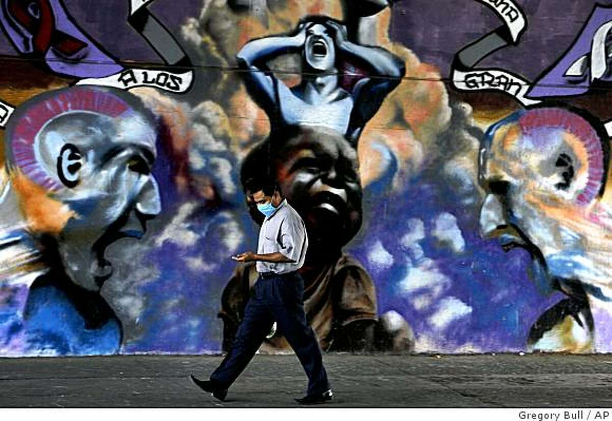 A man, wearing a surgical mask ,passes a mural in Mexico City, Mexico, Friday, April 24, 2009. Mexico closed its schools across its capital after at least 16 otherwise healthy people died and more than 900 others fell ill from what could be a new strain of swine flu.