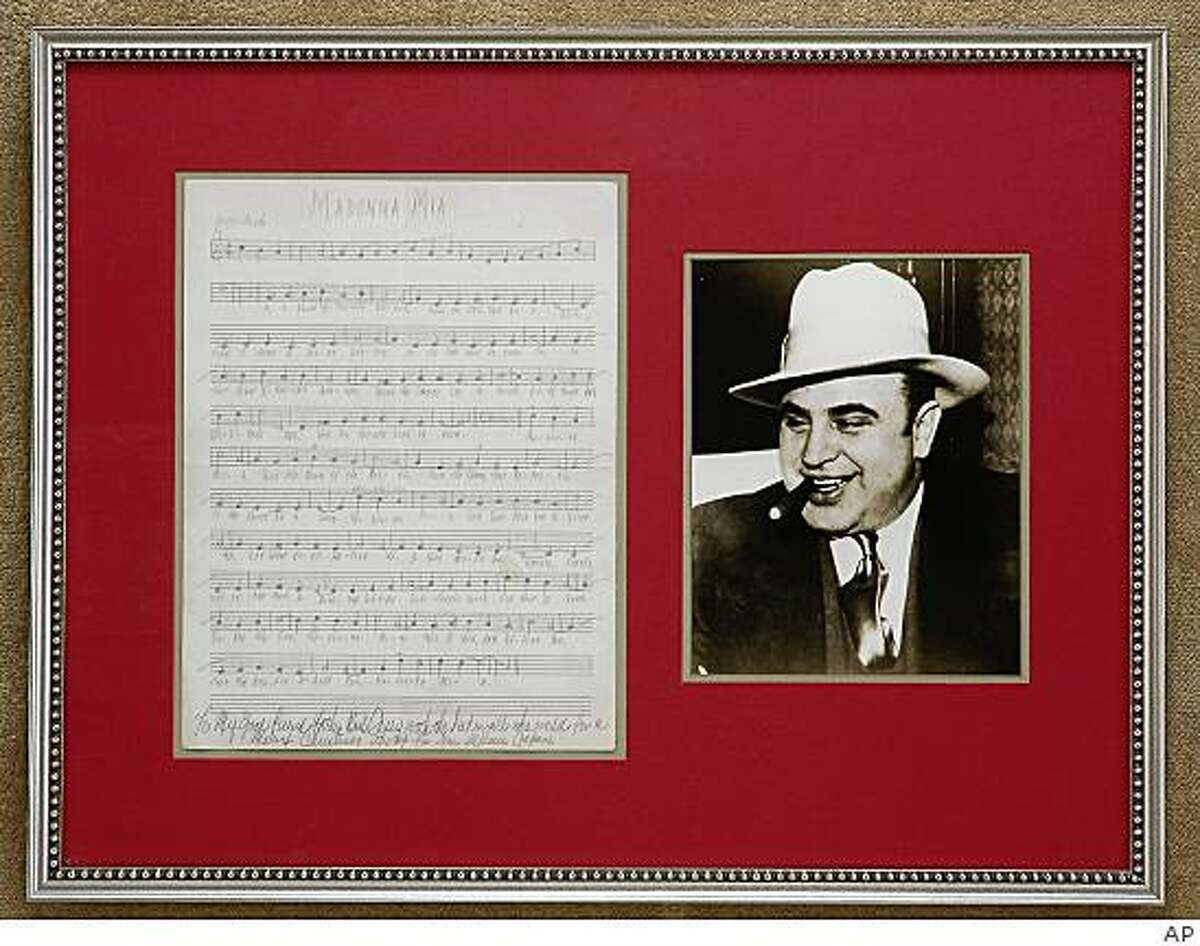 """An undated photo provided April 15, 2009, by Kenneth W. Rendell, Inc., shows a framed photo of Al Capone and sheet music for a song """"Madonna Mia"""" written in pencil by Capone while he was at Alcatraz prison. Today, more than 70 years after Capone penned the song, somebody is recording it for a CD (AP Photo/Kennetth W. Rendell, Inc.) ** NO SALES**"""