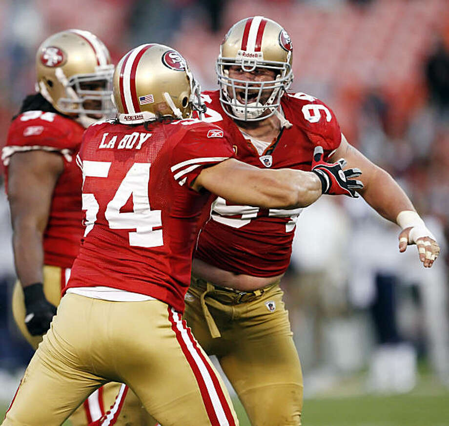 Travis La Boy, left, and Justin Smith celebrate after Smith sacked Rams quarterback Sam Bradford for a loss of 8 yards in overtime at Candlestick Park in San Francisco on Sunday. Photo: Carlos Avila Gonzalez, The Chronicle