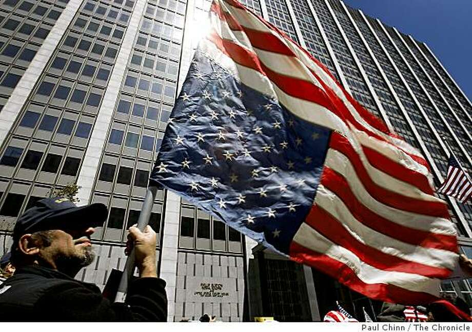 """John Harvan waves an American flag upside down - which signifies distress - as several hundred protesters rally in front of the John Burton Federal Building in San Francisco, Calif., on Tuesday, April 15, 2009 to demonstrate against tax increases. The rally was one of dozens held nationwide that was dubbed the """"Tax Day Tea Party"""". Photo: Paul Chinn, The Chronicle"""