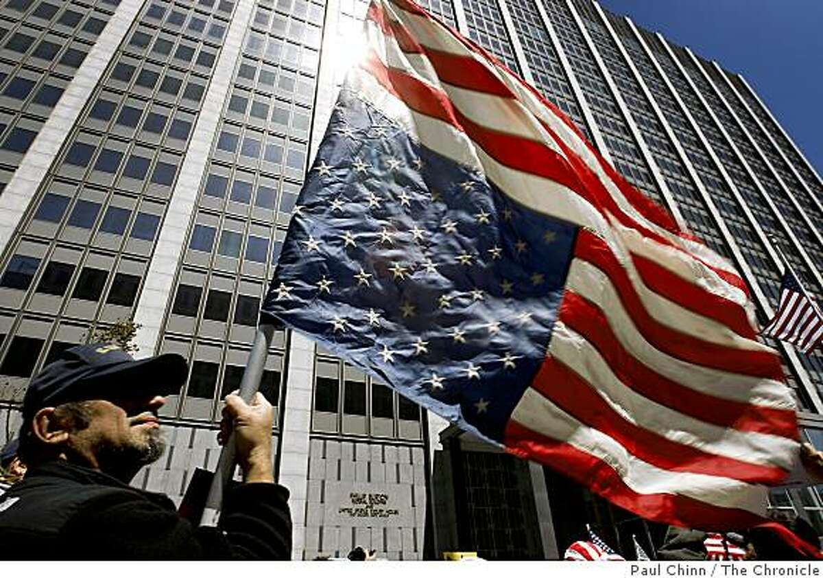 John Harvan waves an American flag upside down - which signifies distress - as several hundred protesters rally in front of the John Burton Federal Building in San Francisco, Calif., on Tuesday, April 15, 2009 to demonstrate against tax increases. The rally was one of dozens held nationwide that was dubbed the