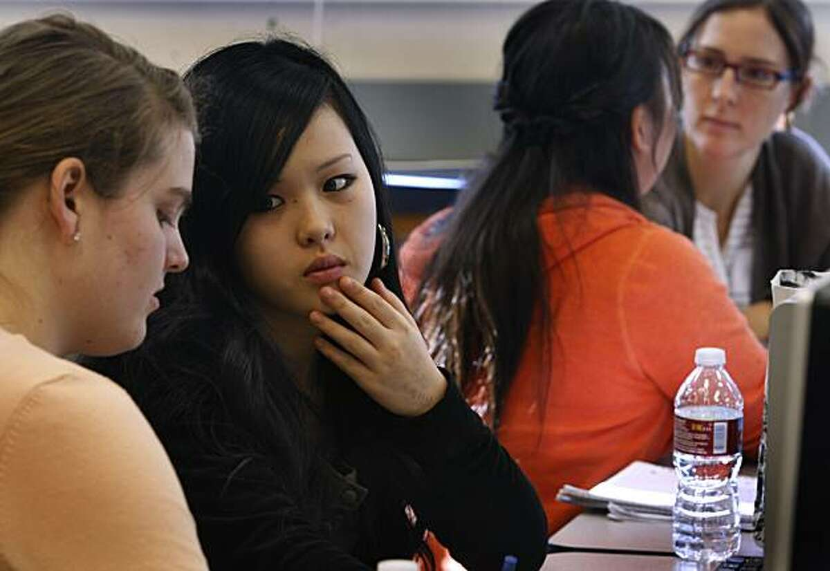 Lia Killeen (left) helps high school senior Irene Noh write a personal statement for her college application while Julie Sims (right) tutors Eowyn Wen at a two-day writing seminar at Mission High in San Francisco, Calif., on Saturday, Nov. 13, 2010.