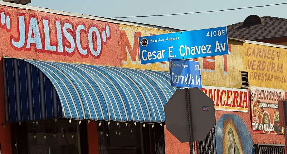Signs in Spanish and English, and the Virgin of Guadalupe, the patron saint of Mexico, are seen at the Jalisco Market on Cesar E. Chavez Avenue in East Los Angeles.(AP Photo/Reed Saxon) Photo: Reed Saxon, Associated Press