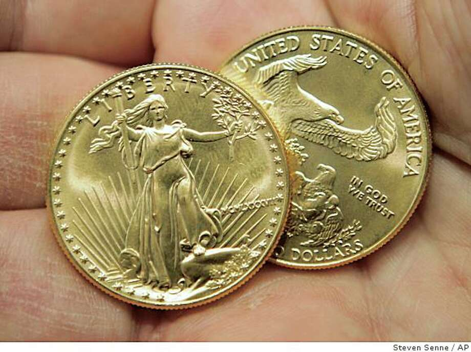 ** FILE ** In this March 13, 2008 file photo, an employee at the Minuteman Coin & Jewelry shop displays two recent American eagle gold coins in Boston. As the worst recession in at least a generation spreads, so too does the clamor for gold bars and coins, assets less likely to go up on smoke like so many derivatives and asset-backed securities. (AP Photo/Steven Senne, file) Photo: Steven Senne, AP