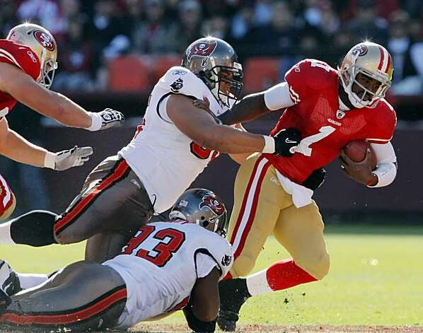 Troy Smith is sacked by Tampa Bay's Al Woods, top, and Gerald McCoy, bottom, in the first quarter at Candlestick Park in San Francisco on Sunday. Photo: Carlos Avila Gonzalez, The Chronicle