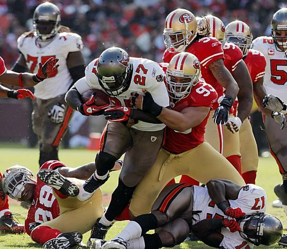 LeGarrette Blount runs through the defensive line in the second quarter as Demetric Evans finally makes the stop. The San Francisco 49ers played the Tampa Bay Buccaneers at Candlestick Park in San Francisco, Calif., on Sunday, November 21, 2010. Photo: Carlos Avila Gonzalez, The Chronicle