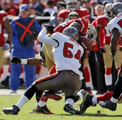 Josh Morgan loses the ball after getting hit by Tampa Bay's Geno Hayes in the first quarter at Candlestick Park in San Francisco on Sunday. Photo: Carlos Avila Gonzalez, The Chronicle