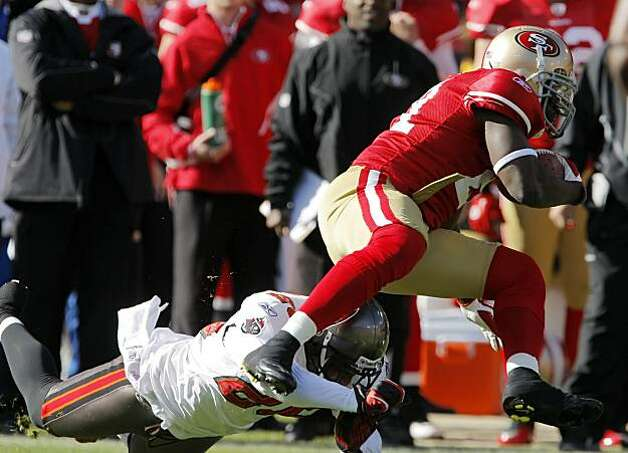 Frank Gore dodges a hit by the Buccaneers' Aqib Talib in the first quarter at Candlestick Park in San Francisco on Sunday. Photo: Carlos Avila Gonzalez, The Chronicle