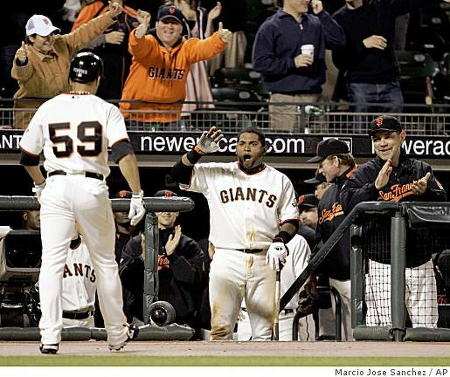 San Francisco Giants' Andres Torres (59) is greeted in the dugout by teammate Pablo Sandoval, center, and manager Bruce Bochy after Torres' solo home run off Arizona Diamondbacks relief pitcher Scott Schoeneweis in the eighth inning of a baseball game in San Francisco, Friday, April 17, 2009. (AP Photo/Marcio Jose Sanchez) Photo: Marcio Jose Sanchez, AP