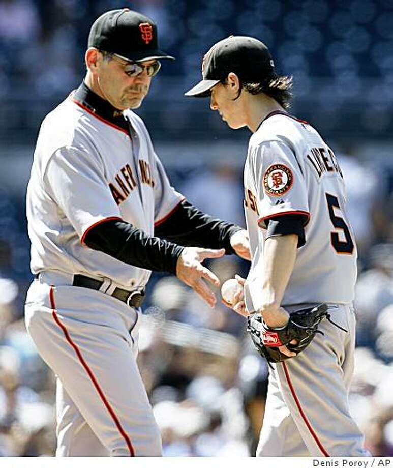 San Francisco Giants manager Bruce Bochy, left, takes the baseball from pitcher Tim Lincecum as Lincecum leaves the game in the sixth inning against the San Diego Padres on Sunday, April 12, 2009, in San Diego. The Padres won 6-1. (AP Photo/Denis Poroy) Photo: Denis Poroy, AP