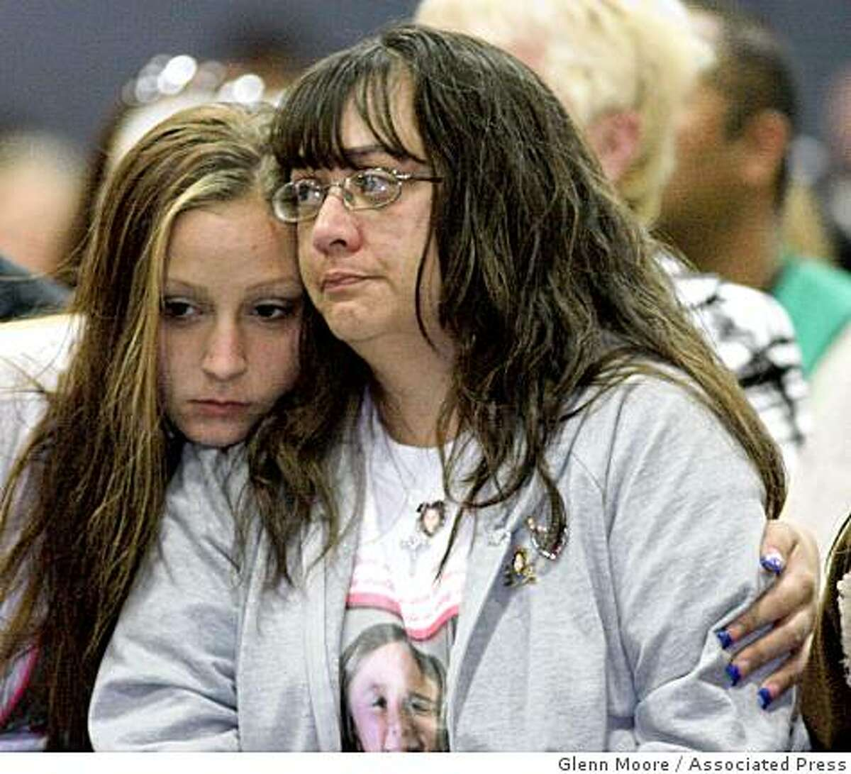 Maria Chavez, right, is embraced by her daughter Miranda during a memorial service for her slain daughter Sandra Cantu on Thursday in Tracy.