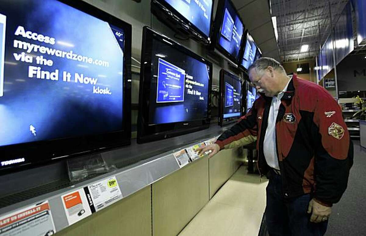 Doug Pongrazc checks out a large screen television while shopping at a Best Buy store in Elk Grove, Calif.