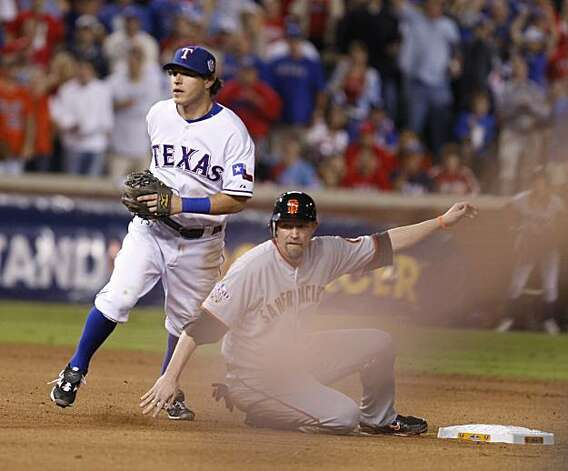 San Francisco Giants first baseman Aubrey Huff looks back to first base as Texas Rangers second baseman Ian Kinsler completes a double play in the fifth inning of Game 5 of the World Series on Monday. Photo: Lance Iversen, San Francisco Chronicle