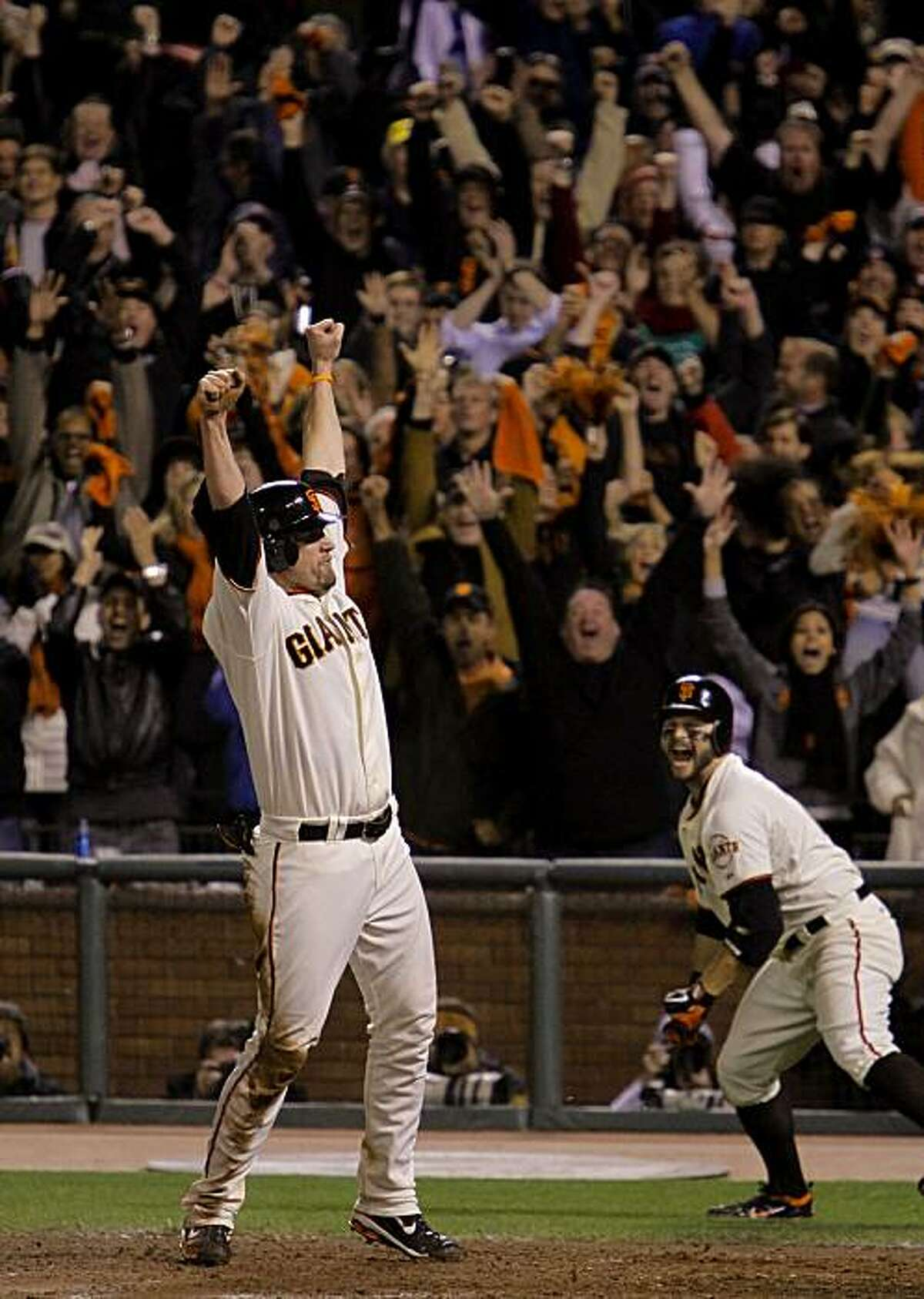 Giants Aubrey Huff, scores the winning run on a fly ball by Juan Uribe in the bottom of the ninth inning, as the San Francisco Giants beat the Philadelphia Phillies 6-5, to take game 4 of the National League Championship Series, on Wednesday Oct. 20, 2010 at AT&T Park, in San Francisco, Calif. Teammate Cody Ross reacts to the win at right.