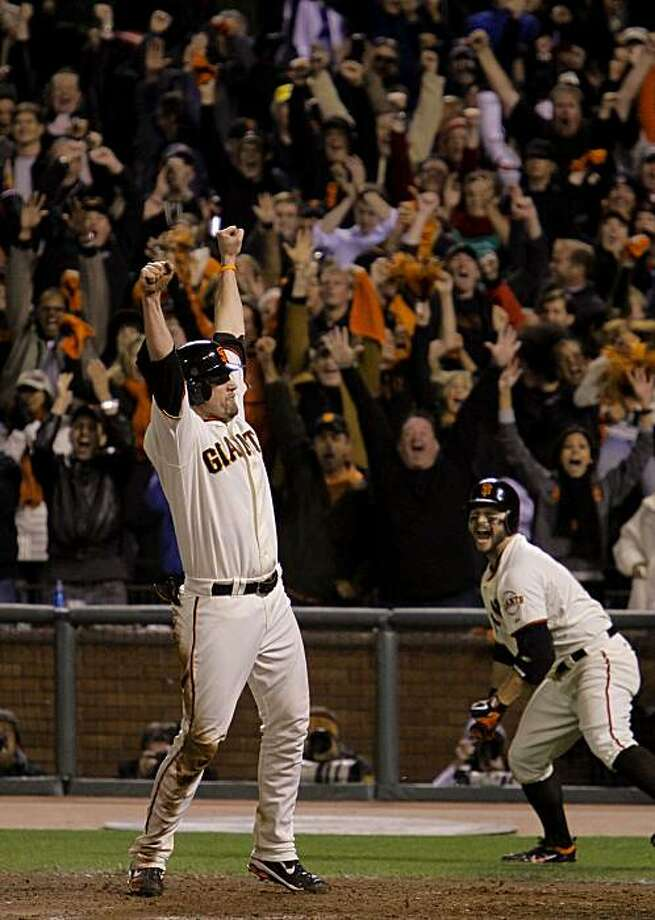 Giants Aubrey Huff, scores the winning run on a fly ball by Juan Uribe in the bottom of the ninth inning, as the San Francisco Giants beat the Philadelphia Phillies 6-5, to take game 4 of the National League Championship Series,  on Wednesday Oct. 20, 2010 at AT&T Park, in San Francisco, Calif. Teammate Cody Ross reacts to the win at right. Photo: Michael Macor, The Chronicle