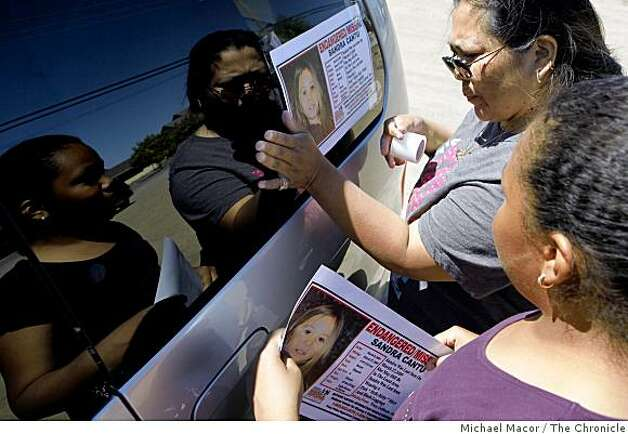 Corina Cottier and her 11-year-old daughter, Vinnecia, of Tracy,  tape fliers onto their mini-van as they join hundreds of volunteers who join a search for missing 8-year-old Sandra Cantu, in Tracy, Calif., on Saturday April 4, 2009. Photo: Michael Macor, The Chronicle